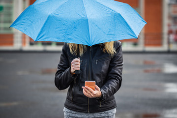 Woman with umbrella holding smart phone and standing in rain at street
