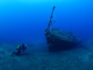 Foto auf Acrylglas Schiffbruch scuba divers exploring ship wreck scenery underwater shipwreck metal on the ocean floor