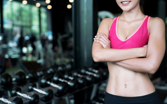 Closeup pictures of young woman in relaxed sports clothing after exercising at the gym, The girl with the abdominal muscles, Six Pack.