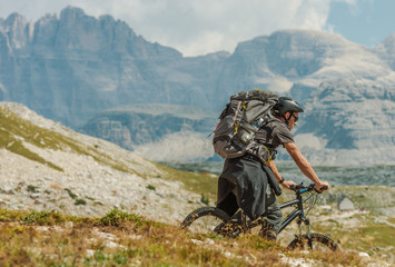 Wall Mural - Biker with Backpack Riding on the Mountain Trail