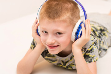 young boy is listening music with ehadphone lying on the sofa at home