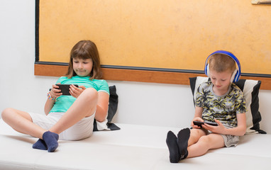 Sister and brother playing online games on smartphone at home