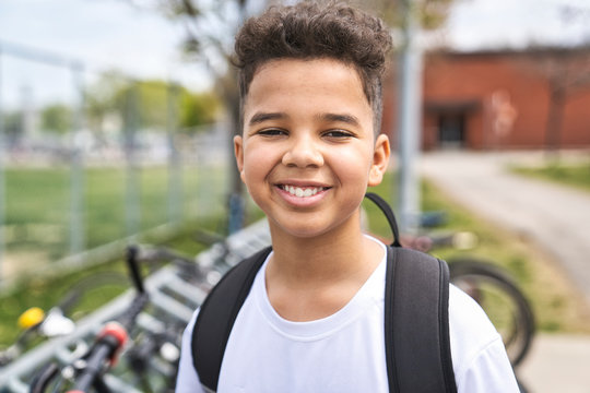 boy riding bike wearing a helmet outside at school playground