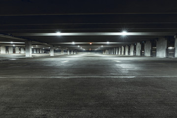 Grungy, dimly lit empty parking garage with overhead lights and an exit sign hanging from the ceiling. Fototapete