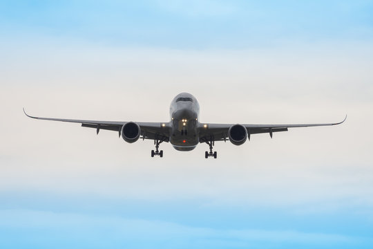 A heavy passenger airplane on final approach on a cloudy day.