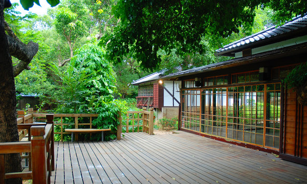 Traditional asian architecture with wooden terrace in green surrounding