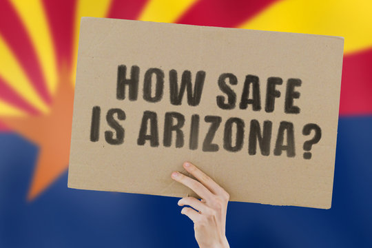 """The phrase """" How safe is Arizona? """" on a banner in men's hand with blurred Arizona's flag on the background. Safety in the city. Violence. Attacks. Security on the street. Crime situations"""