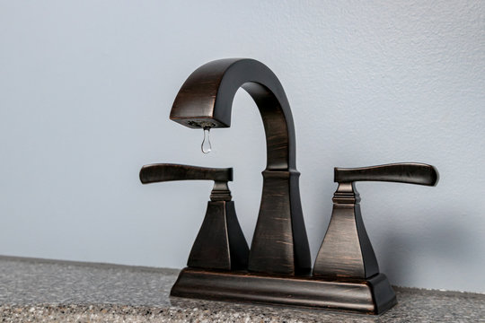 Bathroom faucet sink with water dripping. Concept of DIY home repair, plumbing maintenance, clean water, water conservation