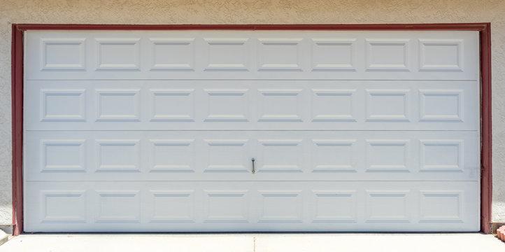 A white garage door installation on a suburban house