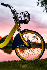 Papiers peints Velo Front wheel of a yellow bike on the lake. Sunset.