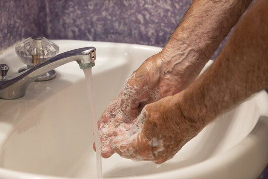 Close up soapy hands running water in sink