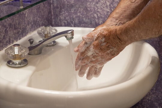 Rubbing hands with soap running water in bathroom sink