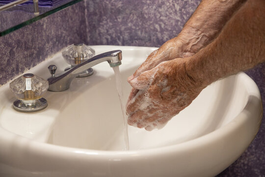 Soaping hands with running water bathroom sink horizontal