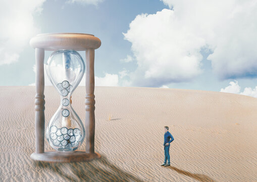 man before hourglass, in the desert, watching time run out. End of time concept, doomsday and fulfillment of biblical prophecies