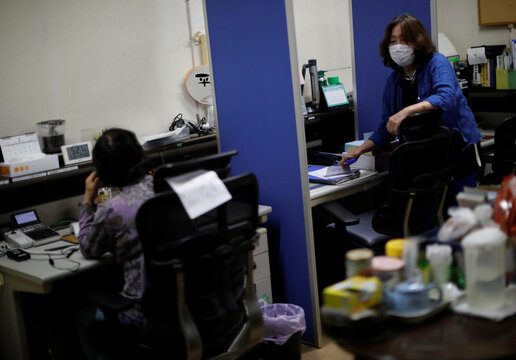 Machiko Nakayama, director of the Tokyo Befrienders call center,  and a volunteer handle an incoming call during the spread of the coronavirus disease (COVID-19) continues, in Tokyo