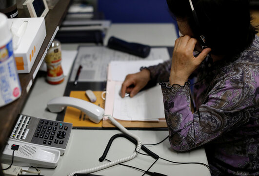A volunteer responds an incoming call at the Tokyo Befrienders call center, a Tokyo's suicide hotline center, during the spread of the coronavirus disease (COVID-19), in Tokyo