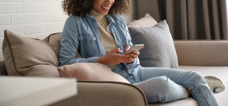 Smiling afro american millennial woman user holding smart phone watching video, playing game, shopping, chatting in mobile technology application sitting on sofa at home. Close up view, banner design.