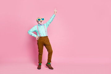 Full length photo of crazy grandpa senior meeting rejoicing direct finger up empty space wear specs suspenders shirt violet bow tie pants shoes socks isolated pastel pink color background