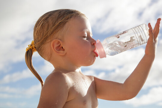 Toddler girl drinking water from the baby bottle