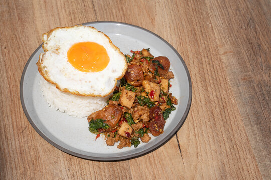 Closed up Famous Thai food padkaprow.  A plate of delicious Stir fried  fresh holy basil mix pork minced and sausage with toped rice fried egg on wooden background.