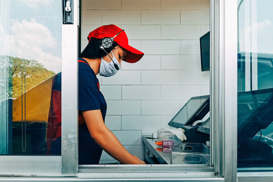 Bangkok, Thailand - May 28, 2020 : fast food cashier in drive thru service wearing hygiene face mask to protect coronavirus pandemic or covid-19 virus outbreak working on counter at the station.