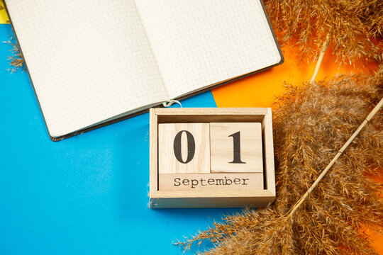 Calendar of wooden cubes with numbers and months. Notepad with white sheets. The first day of the school year. Choosing a number on a wooden calendar. September 1. September date