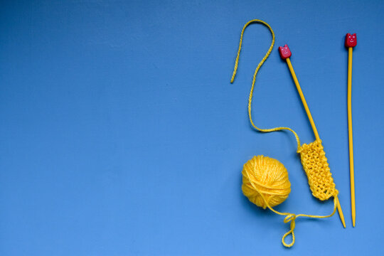 Learn to knit fun yellow needle and yarn on blue background