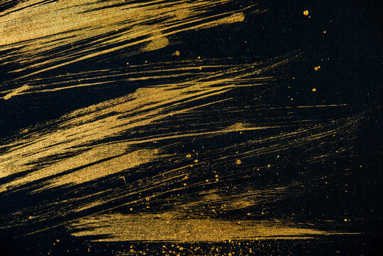 strokes with golden paint brush on black paper.