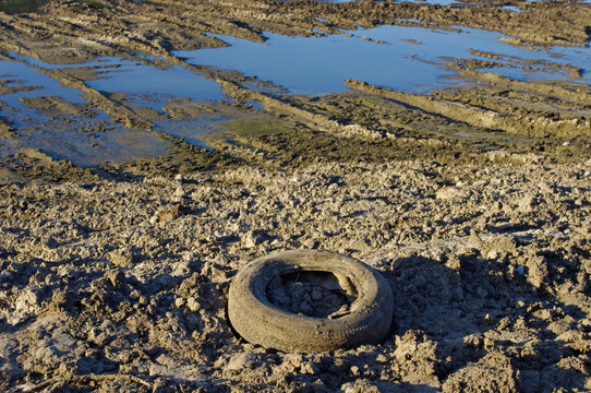 old tire on the edge of a drained reservoir
