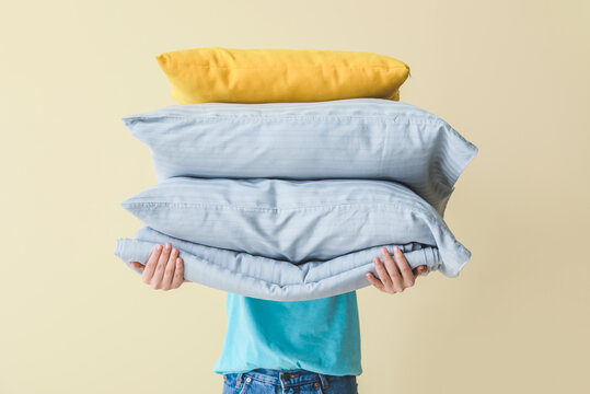 Woman holding pillows and bed sheets on color background