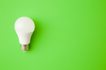 One white led light bulb on bright green table background. Closeup. Energy saving. Empty place for text or logo. Top down view.
