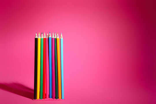 Colorful pencils with drawn faces on pink background. Unity concept