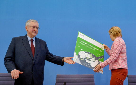 German Minister for Food and Agriculture Julia Kloeckner and Manfred Guellner, Managing Director of Forsa Institute for Statistical Analysis, present a placard at the beginning of a news conference in Berlin