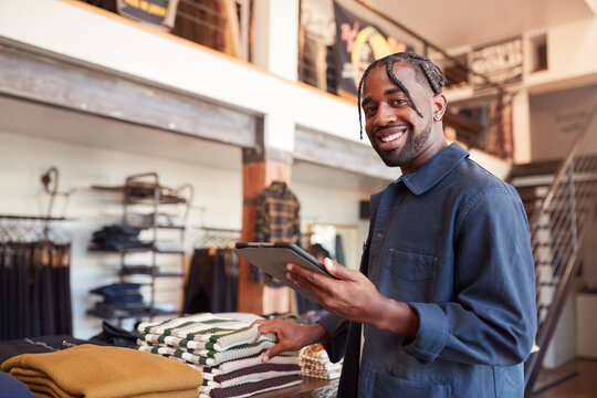 Portrait Of Male Owner Of Fashion Store Using Digital Tablet To Check Stock In Clothing Store