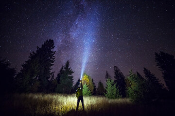 Wall Mural - Silhouette of climber standing against the Milky Way with a flashlight in his hands. Location Carpathian, Ukraine, Europe. Astrophotography of milkyway. Dramatic scene. Discover the beauty of earth.