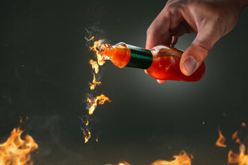 Burning chili sauce pouring out of a bottle