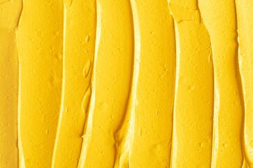 Yellow cosmetic facial mask (cream, body scrub) texture close up, selective focus. Abstract...