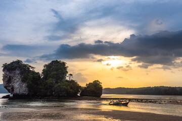 Traditional thai longtail boat at sunset beach. Ao Nang, Krabi province.