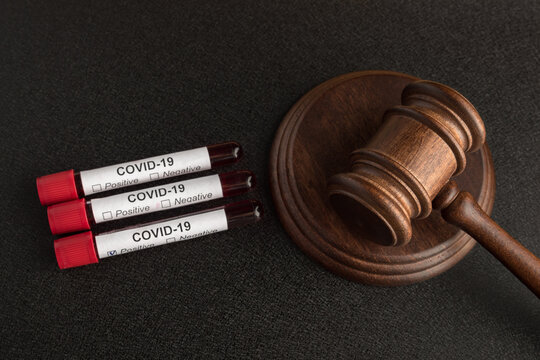 Infected blood samples in tubes COVID 19 and judge's gavel. Punishment for the spread of infection