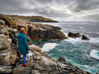 Wall Mural - A woman and her dog stand on rugged cliffs at Hushinish on the Isle of Harris