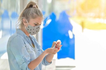 Portrait of a woman wearing protective mask against coronavirus and applying hydroalcoholic protective lotion on her hands