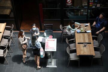 A waitress checks a customer's body temperature before entering a restaurant, amid the coronavirus disease (COVID-19) outbreak in Kuala Lumpur