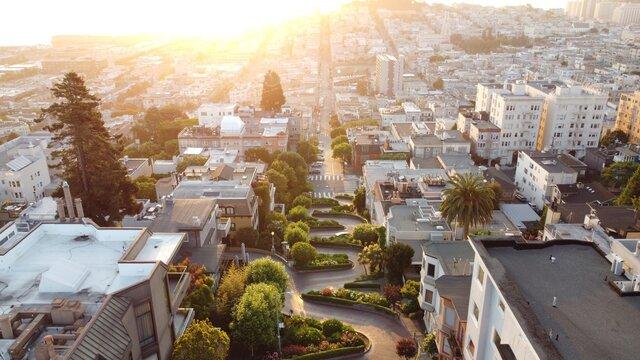 Aerial shot of the maze-like Lombard street glowing under the sun rays in San Francisco California