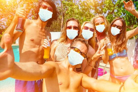 attractive six friends making self portrait on smartphone in swimmingpool