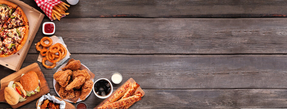 Selection of take out and fast foods. Corner border banner. Pizza, hamburgers, fried chicken and sides.  Overhead view on a dark wood background with copy space.