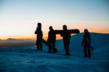 Four people carrying snowboards along a snowy landscape with the sunset in the background.