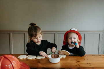 Two children dressed as firefighters at a table decorating  cookies with chocolates and sprinkles.