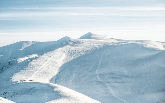 View of deserted ski slopes in the mountains, empty pistes with snow tracks.