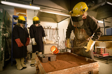 Three people wearing overalls and protective equipment watching one pouring molten metal into a mold.