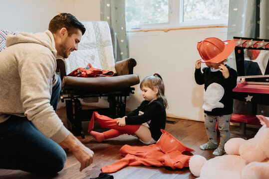 A father helping his two children getting dressed up as firefighters.